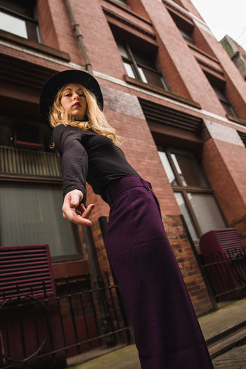 Fashion Hat Architecture Attractive Beautiful Woman Blonde Girl Clothing Come Here Fashion Photography Fingers Hand Hold Hold My Hand..... Lifestyles Looking At Camera Low Angle View Portrait Purple Reaching Reaching Out Standing Trousers Young Adult Young Women