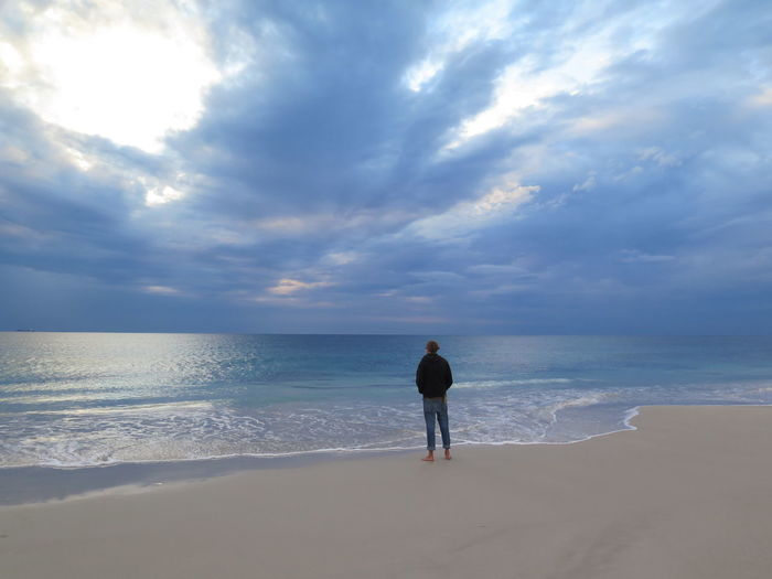 Full Length Of Man Standing On Shore At Beach Against Cloudy Sky During Sunset
