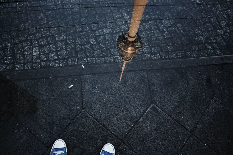 Low section of person on street with reflection of fernsehturm on puddle