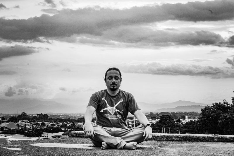 at peace Playing With Filters Heredia, Costa Rica Walking Around Walking Around Taking Pictures Barva Black And White One Person Streetphotography Street Santa Lucía Self Portrait Monochrome Pinhole Photography Morning Meditation Meditate Costa Rica Tied Hair Man Bun Sitting Men Full Length Old-fashioned Portrait Front View Sky Cloud - Sky Calm