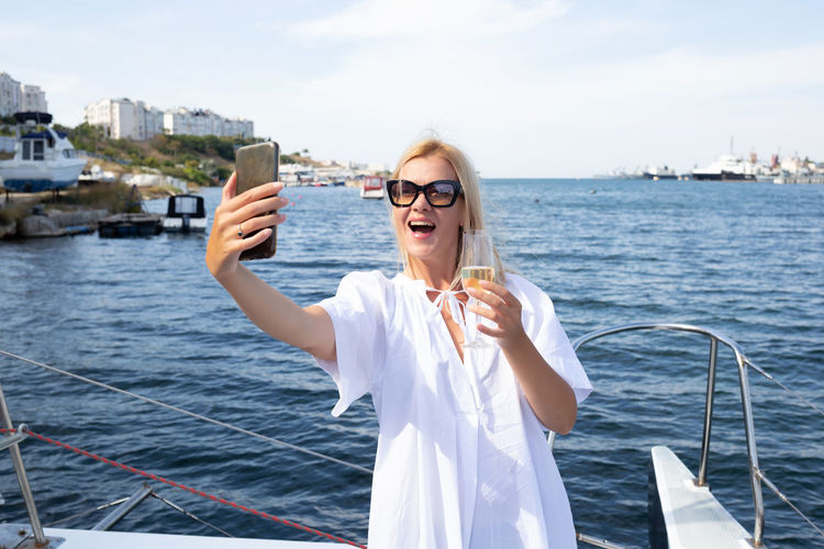 Young woman taking selfie in sea