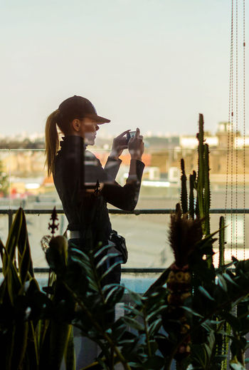 Woman photographing while standing on city against sky