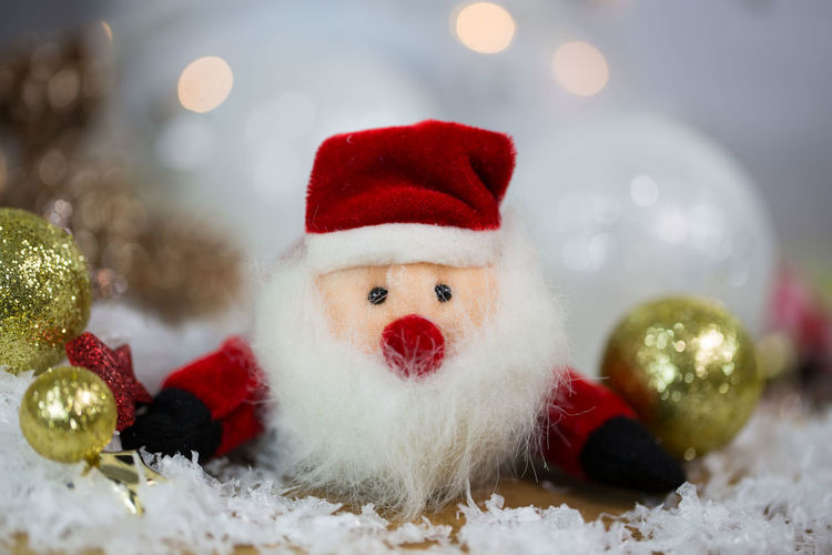 Close-up of christmas ornaments and santa claus figurine on table