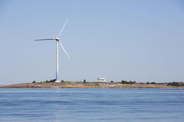 Wind turbines on land against clear sky