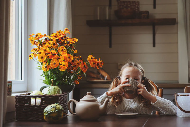 child girl having breakfast at home in autumn morning. Real life cozy modern interior in country house. Breakfast Farm Morning Rural Sweden Tea Cabin Child Childhood Country Life Cozy Drink Girl Home Interior House Hygge Indoors  Interior Lifestyles One Person Portrait Real People Sitting Table