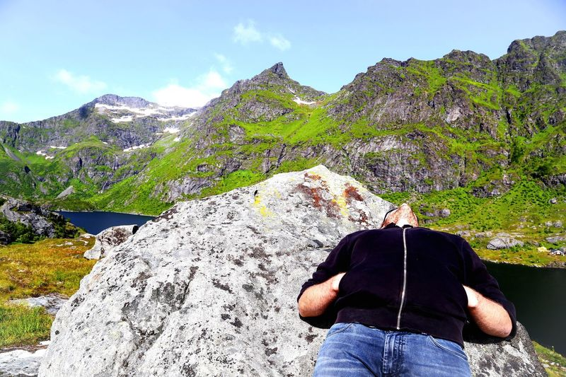 Man Resting On Rock By Mountains Against Sky