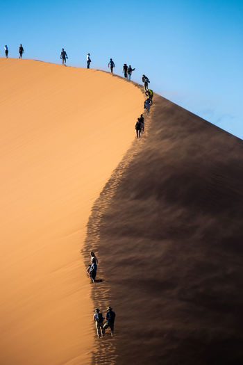 People walking on sand dune against clear blue sky