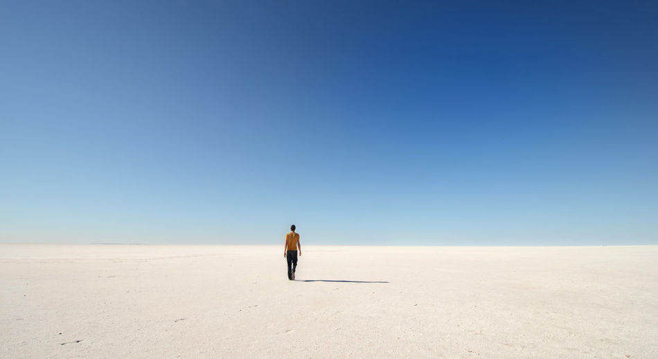 Full length rear view of shirtless man walking on lake mackay against clear blue sky