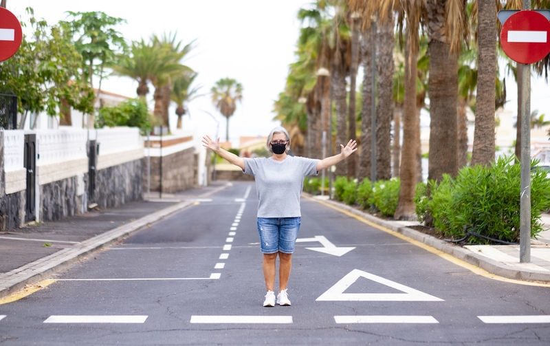 Full length of woman with arms outstretched standing on road