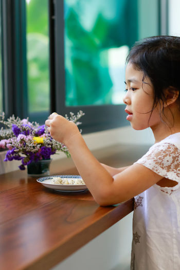 Girl holding ice cream on table