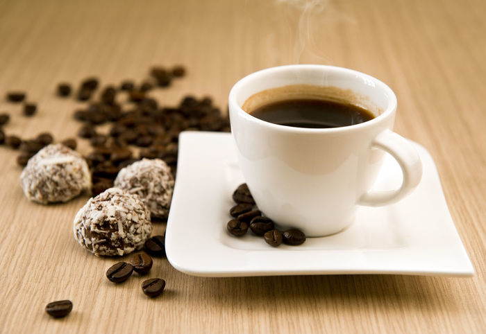 Cup of coffee with beans and truffles over wooden background Breakfast Candle Chocolate Coffee Coffee Time Coffee ☕ Candy Chocolate Candy Close-up Coffee - Drink Coffee Bean Coffee Beans Coffee Break Coffee Cup Coffeine Drink Energy Indoors  No People Nobody Non Alcoholic Beverage Non Alcoholic Drink Refreshment Table Truffle