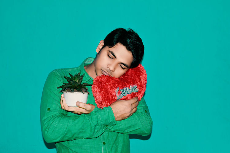 Man Holding Potted Plant And Heart Shape Cushion Against Green Background