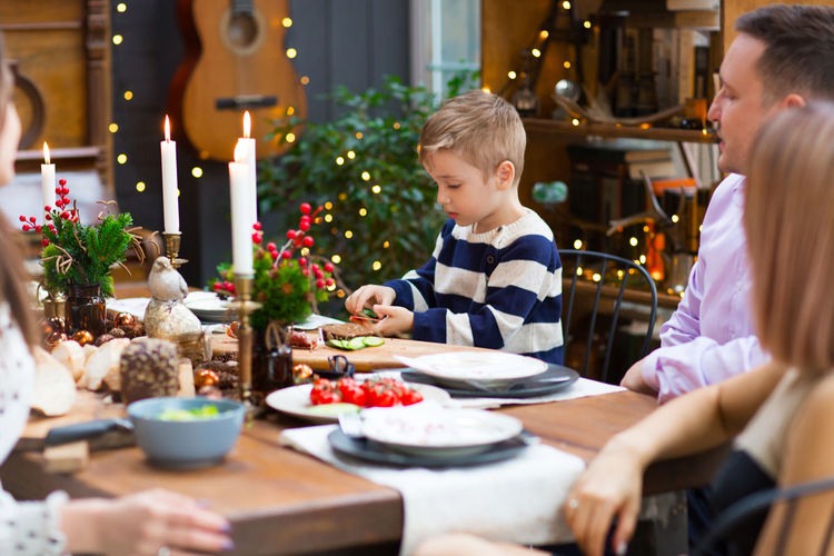 Cute boy sitting at dining table with family