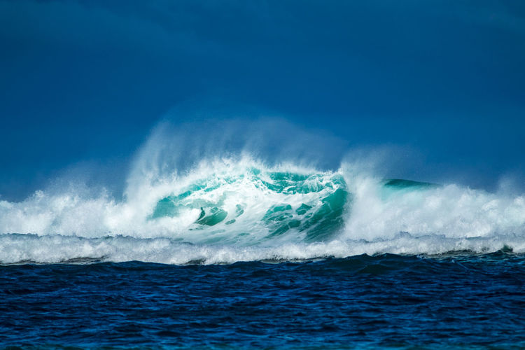 Wave in sea against blue sky