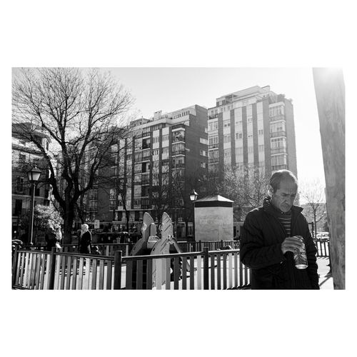 Man standing by buildings in city against sky