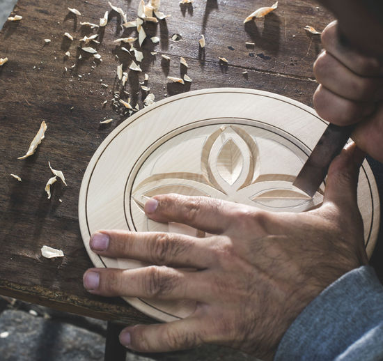 Cropped hands of artist carving wood in workshop