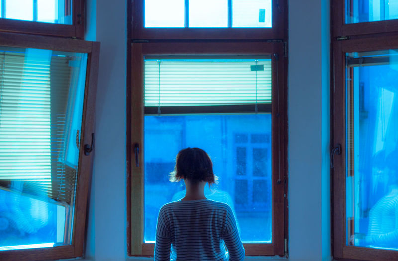 Woman With Short Hair Standing In Front Of Glass Window At Home