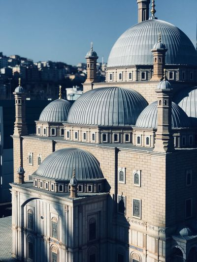 Mosque in city during sunny day