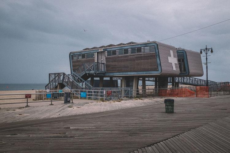 Lifeguard hut on sand against sky