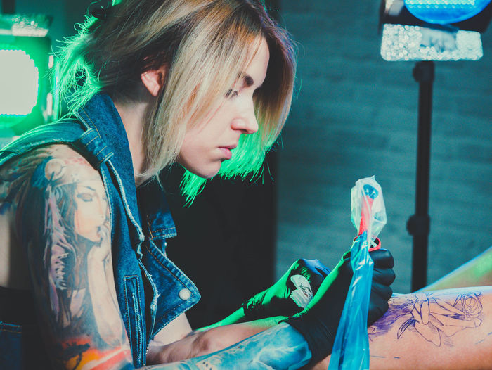 Side view of artist making tattoo on man at studio