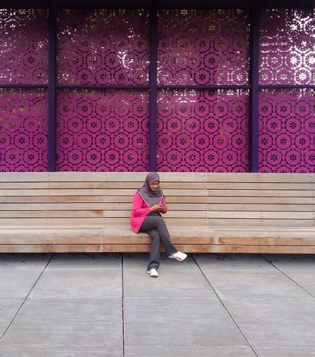 Woman wearing hijab using phone while sitting on bench against pink wall