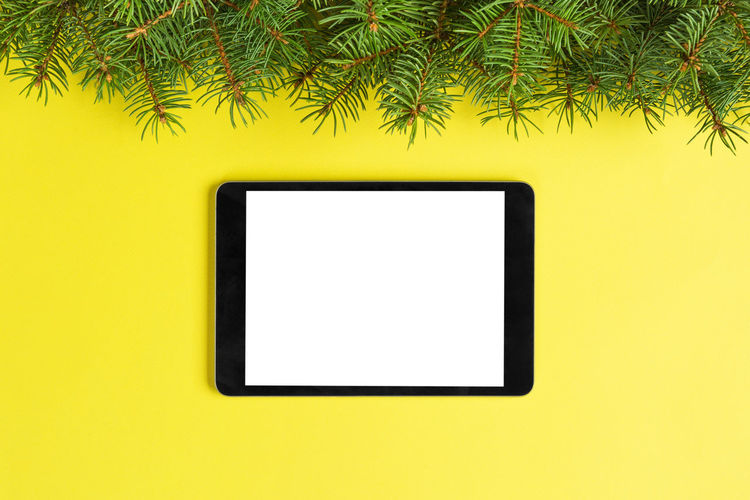 Close-up of smart phone on yellow wall