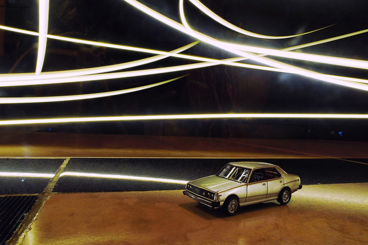 Toy car on illuminated road at night