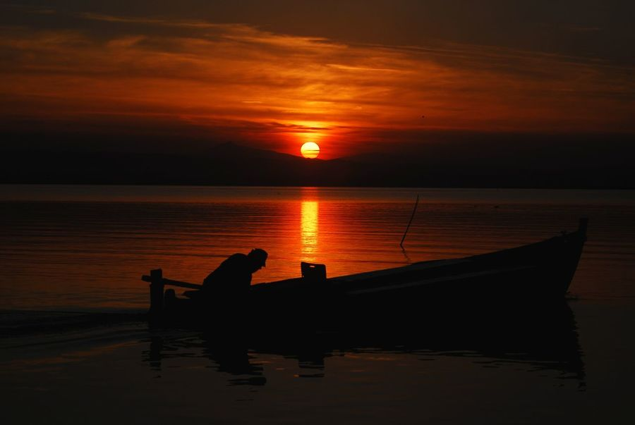 Sunset Nautical Vessel Silhouette Reflection Water Tranquility People Tranquil Scene Sun Nature Idyllic Silence Landscape Aquatic Beauty Floating On Water Relaxation Cloud - Sky Orange Color Day Horizon Nature Horizon Over Water Silhouette