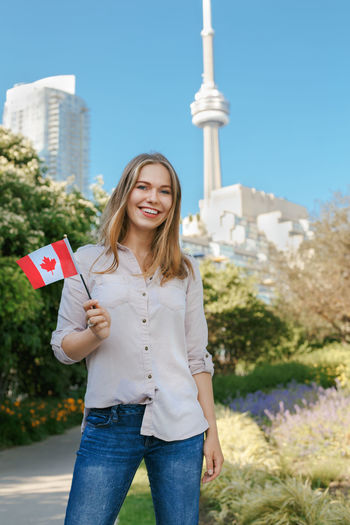 Portrait of smiling woman holding canadian flag while standing against plants