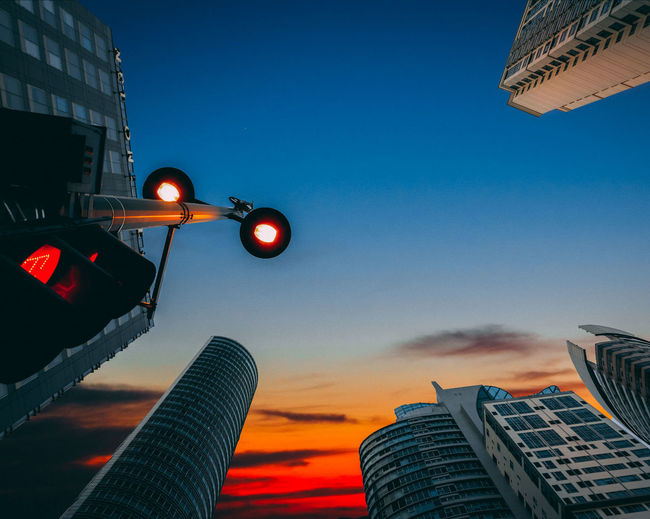 Low angle view of illuminated street light and buildings against sky during sunset