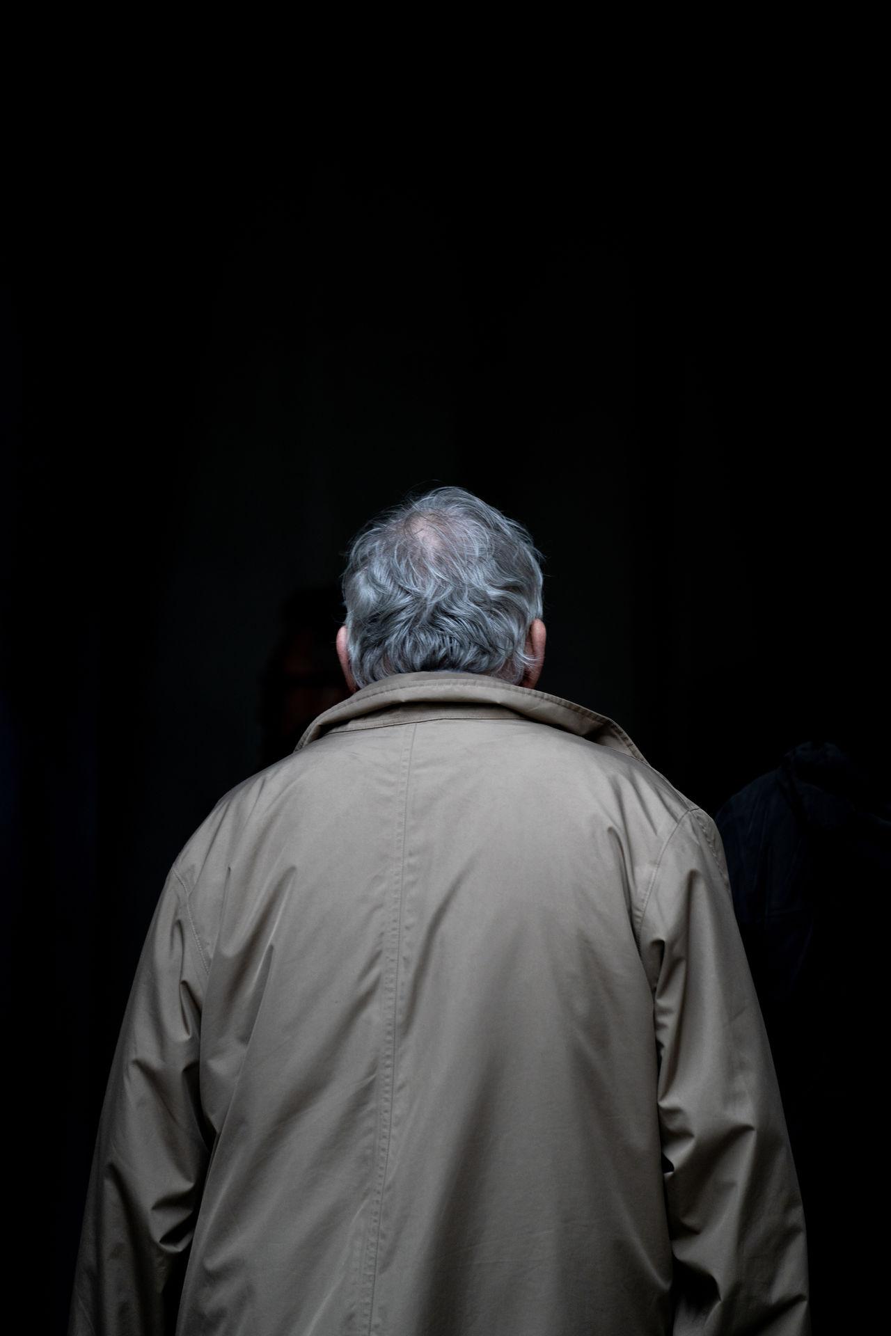 REAR VIEW OF MAN WEARING HAT AGAINST DARK BACKGROUND