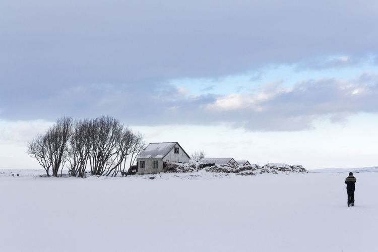 Scenic view of snow covered field by building against sky