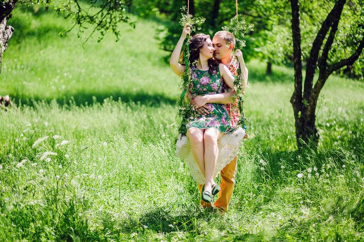 couple relax together in summer forest with swing background. Summer time in green meadow. Outdoors Together Love Dating Couple Relationship Relaxing Leisure Activity Lifestyles Lifestyle Two People Field Green Grass colour of life Picnic Forest Wildflower Summer Spring Happiness Young Adult Nature Summertime Green Color Flower Springtime Village Countryside Meadow Swing Emotion Smiling