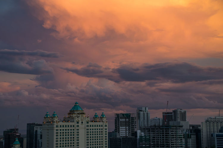 Buildings in city against dramatic sky during sunset