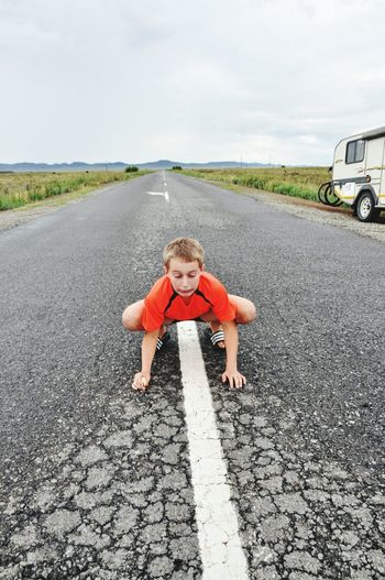 Boy standing on road against sky