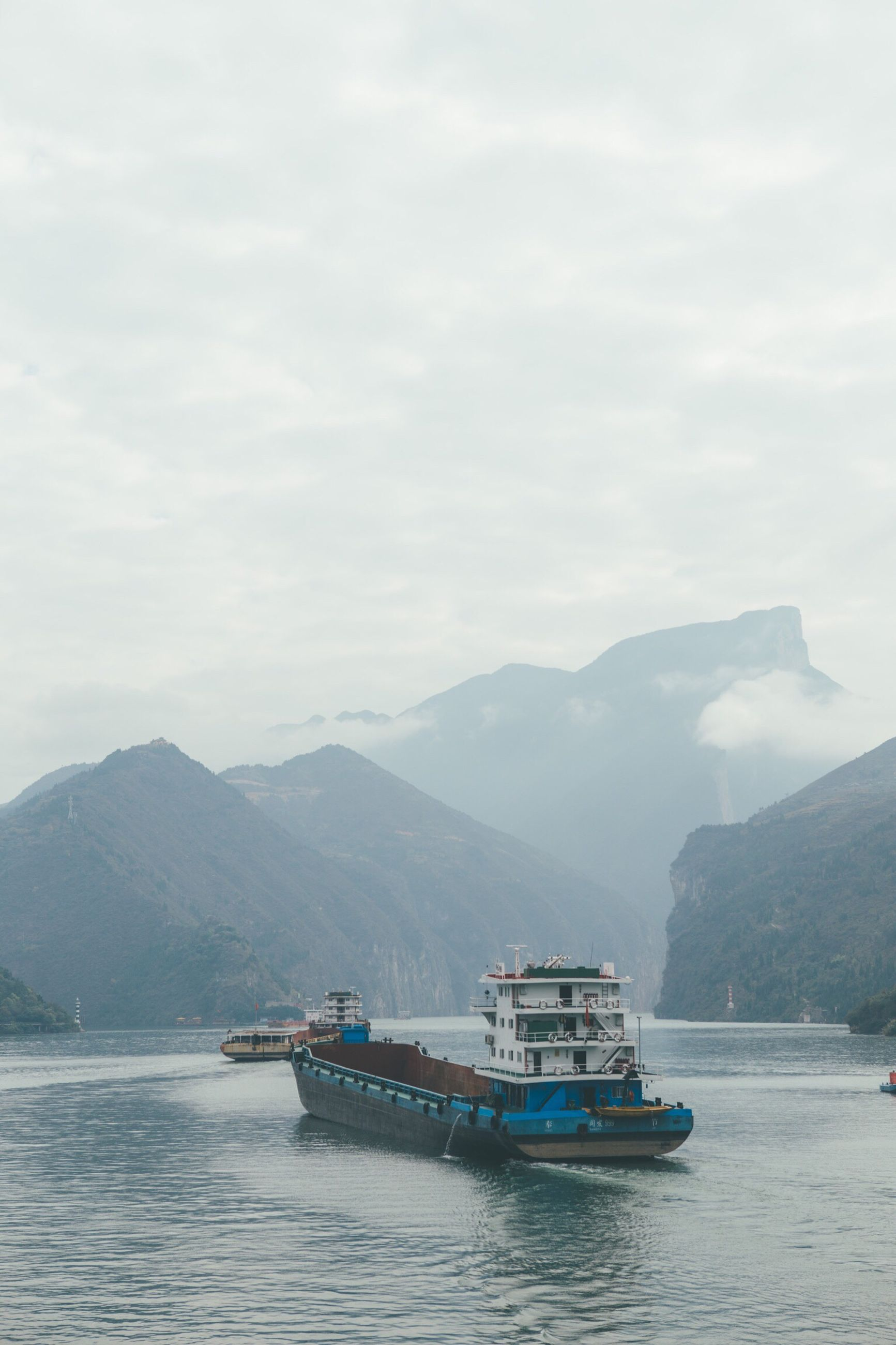 mountain, nautical vessel, transportation, waterfront, water, mountain range, mode of transport, boat, travel, sailing, cloud - sky, sky, tourism, scenics, beauty in nature, passenger craft, nature, journey, travel destinations, tranquil scene, tranquility, fog, ferry, sea, mountain peak, day, ship, outdoors, famous place, non-urban scene, no people, vacations
