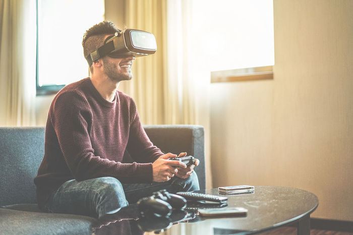 Young gamer playing video games virtual reality glasses in his apartment Gaming Goggles Happy Holidays Man Virtual Young Console Gamer Headset Hipster Joypad Joystick Lifestyles One Person Online  Playing Reality Sitting Technology Video Game  Vr Wireless Technology Young Adult