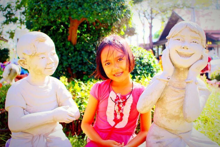 Portrait of smiling girl sitting by statues at park