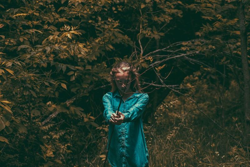Girl holding branch while standing in forest