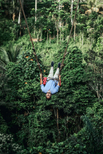 Man hanging on swing in forest