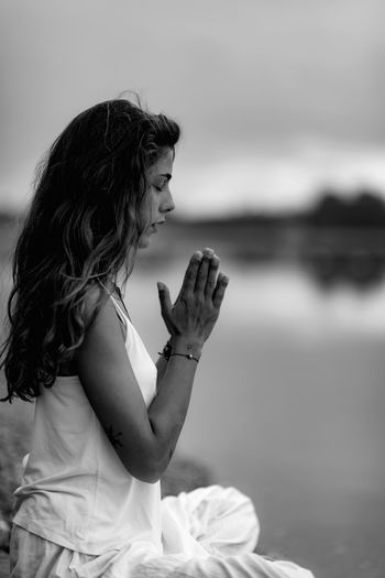 Meditating. Close Up Female Hands Prayer Meditate Yoga Prayer Nature Water Lake Woman Hands Meditation Lifestyles People Relaxation Mindfulness Young Exercise Healthy Beautiful Asana Balance Outdoor Tranquility Spirituality Inner Peace Black And White Female