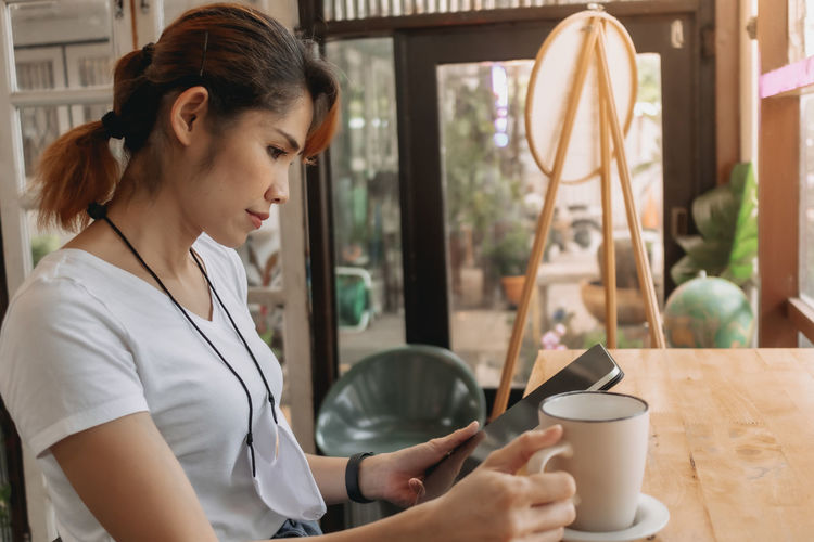 Woman holding coffee cup on table at home