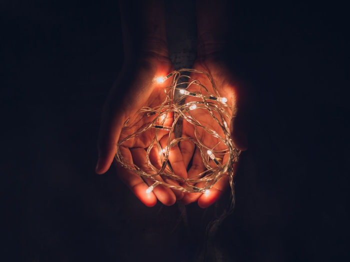 Cropped hands of person holding illuminated string lights against black background