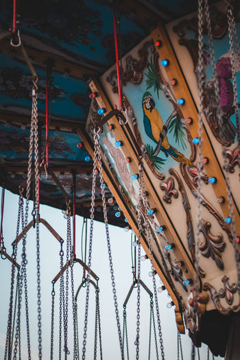 Low angle view of chain swing rides at amusement park