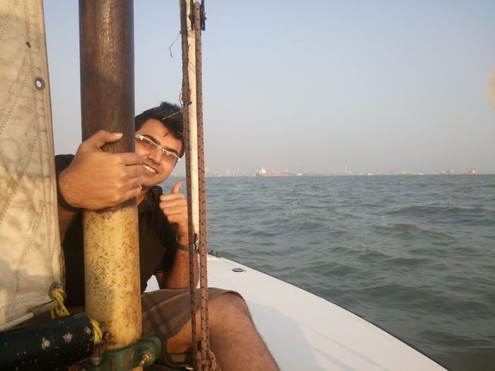 Portrait of young man gesturing thumbs up while sitting in sailboat over sea
