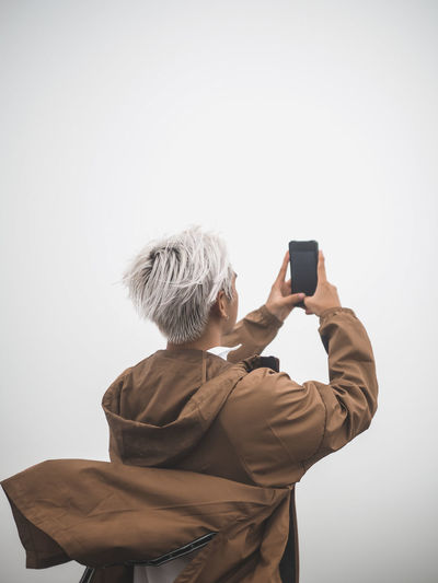 Rear view of person photographing against white background