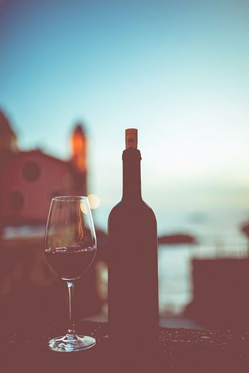 Wineglass and bottle on table against sky