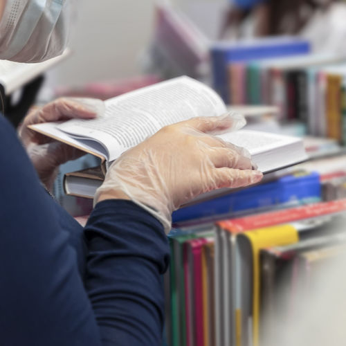 Midsection of woman reading book at bookstore
