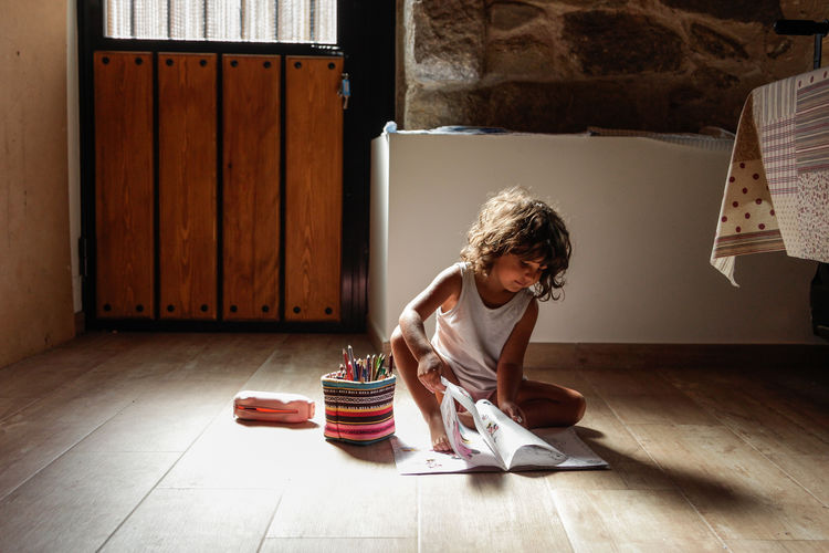 Girl looking down while sitting on hardwood floor
