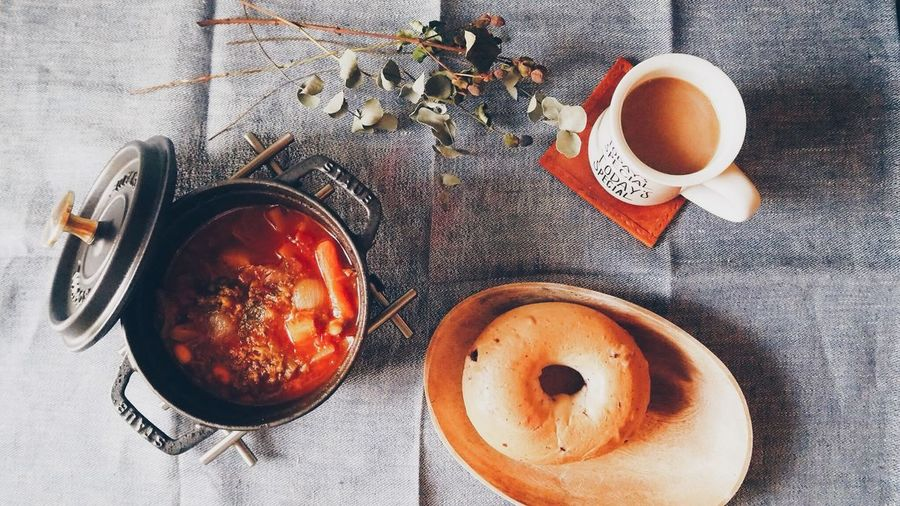High Angle View Of Soup In Cooking Pan And Coffee With Bun